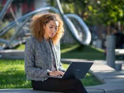 Mujer que trabaja con una computadora portátil en un parque