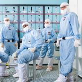 Four people in special suits to wear in clean rooms. Nicknamed