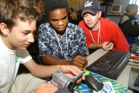 three boys examine multimedia equiment such as a camcorder